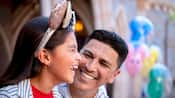 A young girl wearing a Minnie Mouse ears hat shares a laugh with her dad who sits beside her