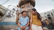 Un niño y una niña se ríen frente a una estructura futurista en Star Wars Galaxy's Edge