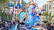 Mickey Mouse in wizard attire stands atop a float in a parade marching near Sleeping Beauty Castle