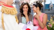 An elated teenage girl in a dress and tiara stands beside her smitten mom while receiving an autograph from Prince Charming
