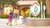 A family of four walks past Goofy's Kitchen restaurant