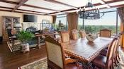 Una larga mesa de comedor de madera con un rústico candelabro de techo al lado de una ventana