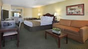 Family suite with a desk, queen bed, nightstands, lamps, tables, chairs, sofa,  art, phone and TV