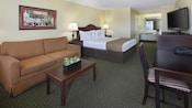 Mini suite con escritorio, cama Queen Size, mesas de noche, lámparas, mesa, sillas, sofá, arte, consola, teléfono y TV
