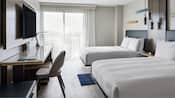 A hotel room features modern furniture that includes 2 double beds, a console, desk, lamps, chairs, an area rug and a flat screen television