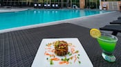A serving of food and a cocktail by the pool area of the Anaheim Marriott Suites