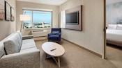 La sala de estar de la suite contemporánea cuenta con un sofá, una lámpara de pie, una mesa de centro, una silla y un televisor montado en la pared