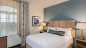 A queen suite bedroom features a queen-size bed with pillows, modern wood headboard, 2 retro style side lamps, 2 nightstands, a dresser, phone and framed art on the walls