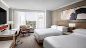 A hotel guest room features 2 queen size beds separated by a nightstand, desk, flat screen television, chairs, lamps, art and picturesque views