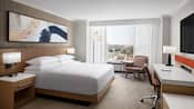 A hotel guest room features a king size bed flanked by nightstands, flat screen television, desk, chairs, lamps, art and a picture window