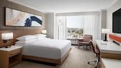 Una habitación de hotel cuenta con una cama King Size rodeada de mesas de noche, una TV de pantalla plana, un escritorio, sillas, lámparas, arte y una ventana panorámica