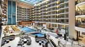 Un patio interior con techo alto en el hotel, con 7 pisos, una piscina cubierta, árboles y asientos