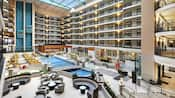 A high ceiling hotel atrium featuring 7 stories, an indoor pool, trees and seating