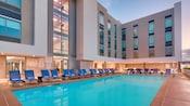 Una fila de camastros rodea la piscina en Hampton Inn and Suites Anaheim Resort Convention Center