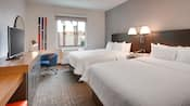 A hotel room with 2 queen size beds, a television and modern design
