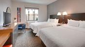 Habitación de hotel con 2 camas Queen Size, televisor y diseño moderno
