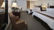 A hotel room with 2 king beds, a chair, a dresser and a desk