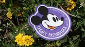 The Legacy Passholder logo sitting on top of a branch of flowers