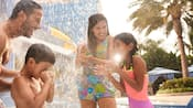 A smiling family of four stands underneath a fountain in the pool play area at the Disneyland Hotel