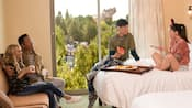 Parents, a boy and a girl enjoying room service food and beverages in their view hotel room