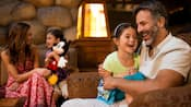 A family of four relax in the lobby of their Disney Resort hotel
