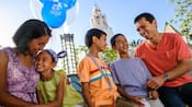 A smiling family of five hangs out together at Disney California Adventure Park with a Mickey balloon in tow