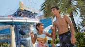 Two children wearing swimsuits, standing near a waterslide at the Disneyland Hotel