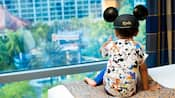 A kid wearing a Mickey ears hat sits on a bed and points toward a window inside the Disneyland Hotel