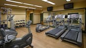 A fitness center with an exercise bike, treadmills, elliptical machine and weight lifting equipment
