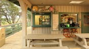 Picnic tables in front of serving windows, a wall menu and condiment station