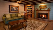 A wood burning fireplace, couch, bookcase and coffee table in a rustic looking room