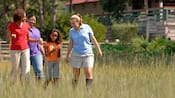 A girl shows her nature discovery to her mom, aunt and a guide