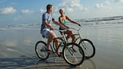 A man and a woman ride bicycles on the beach's wet sand