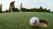 A Mickey golf ball teeters on a hole while a man and his wife admire his putt