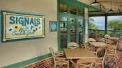 A sign saying 'Signals Seaside Grill' on a wall along an outside patio