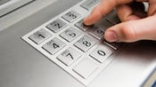 Close-up of fingers pressing numbers on an ATM keypad