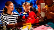 A young boy and a Cast Member admire the boy's craftwork