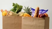 Two paper grocery bags with produce displaying from the top