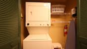 Stacked washer and dryer next to shelves and laundry basket