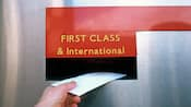 A hand putting a letter into a First Class & International mail slot