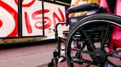 Close-up of wheelchair with a child as passenger, near lift entrance of a Disney bus