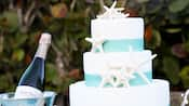 A wedding cake with seashell decorations next to a silver bucket with champagne