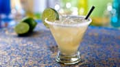 A margarita on the rocks in a glass with a salted rim garnished with a slice of fresh lime