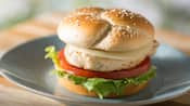 A grilled chicken breast on a bun with lettuce, tomato and cheese