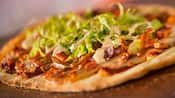 Bacon pieces, shredded lettuce, sliced tomatoes and a creamy dressing atop a crisp flatbread