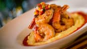 Grilled shrimp accented with a dollop of minced tomatoes, onions and peppers atop creamy cheese grits
