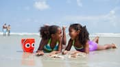 Two laughing girls lie on their stomachs in the wet sand at the beach