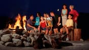 A group of adults and children roasting marshmallows and enjoying themselves at a large campfire A group of adults and children roasting marshmallows and enjoying themselves at a large campfire
