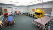 A large recreation room with long tables and sun piñata hanging from a rope