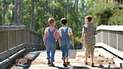 A trio of young male Guests clad in country wear cross a bridge while carrying fishing supplies
